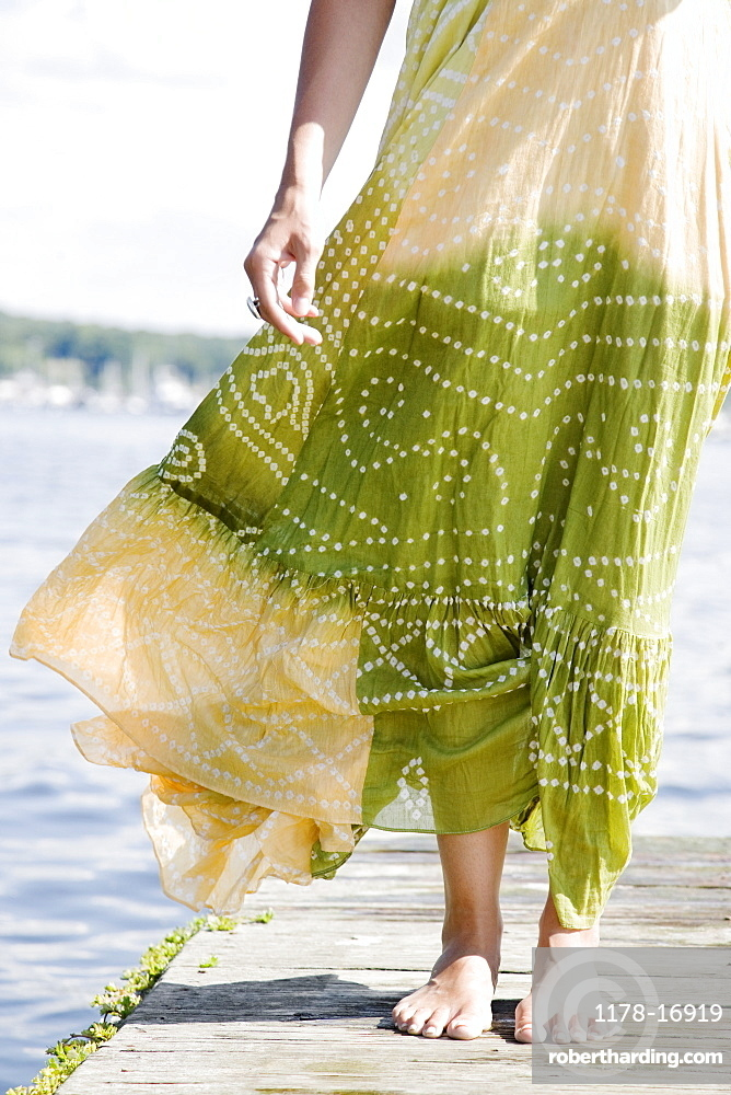 Wind blowing dress of woman standing on dock