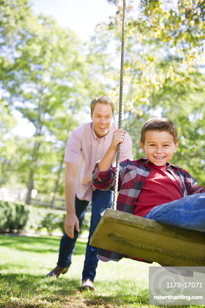 USA, New York, Flanders, Father and son (8-9) playing in garden