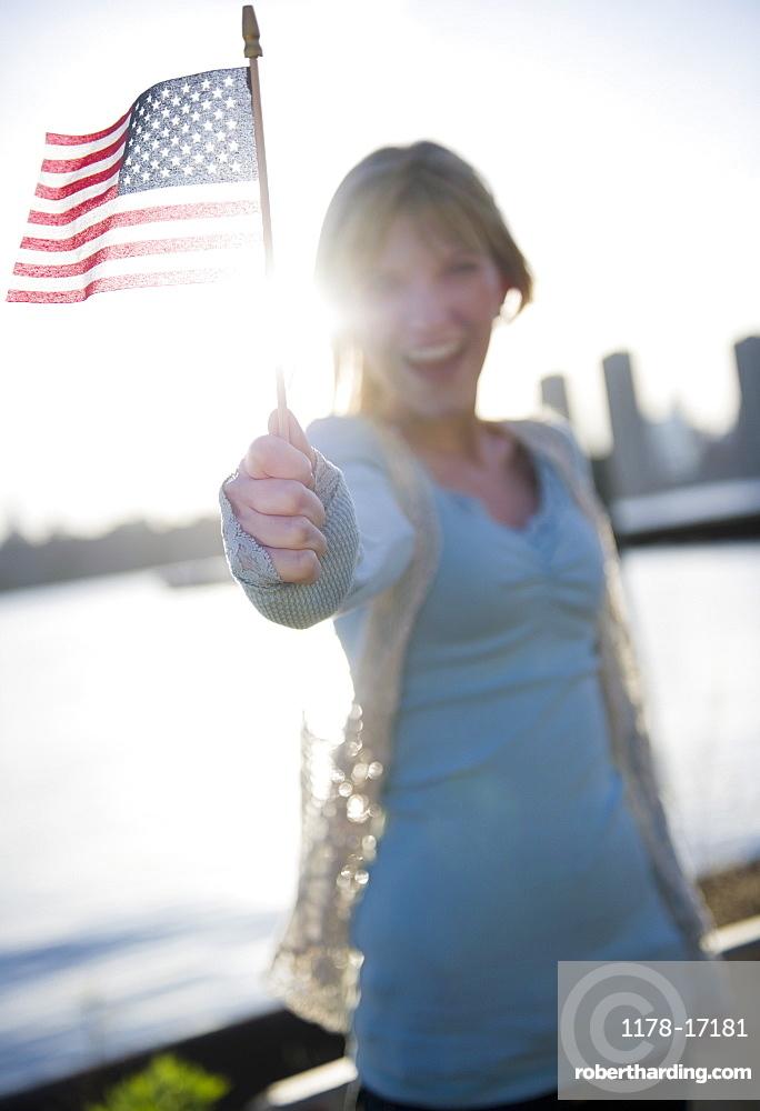 USA, Brooklyn, Williamsburg, Woman holding American flag