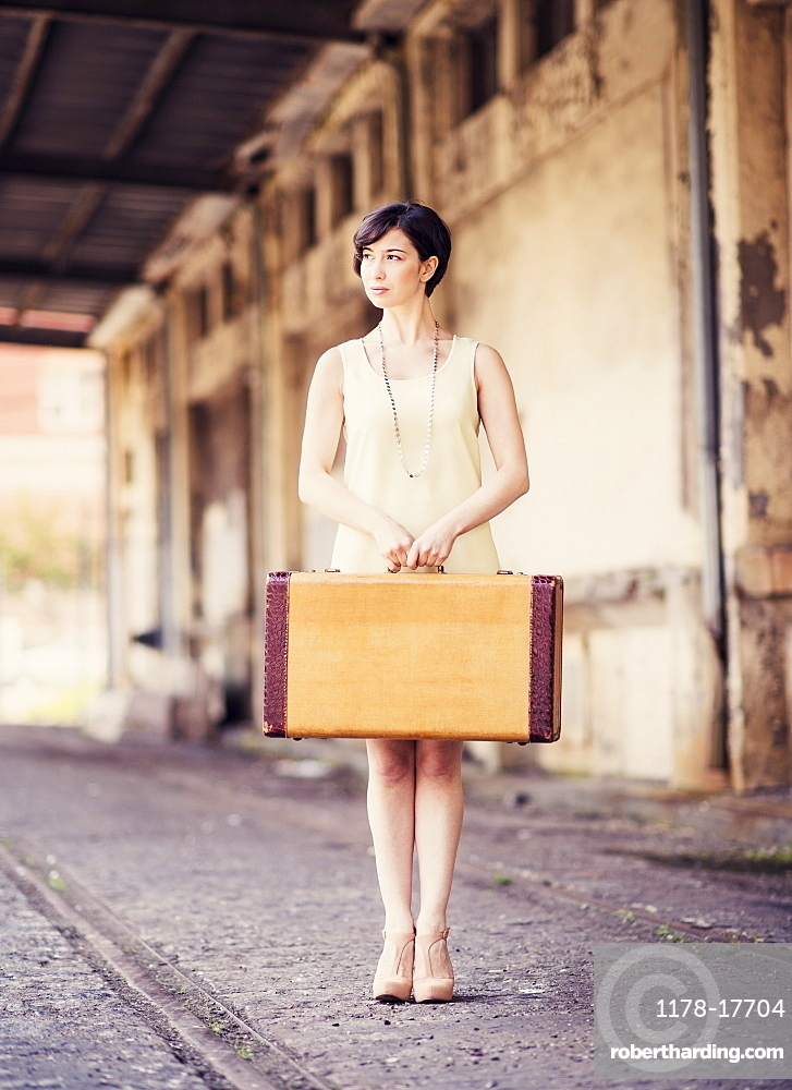 Woman in dress holding suitcase at train station, USA, New Jersey, Jersey City