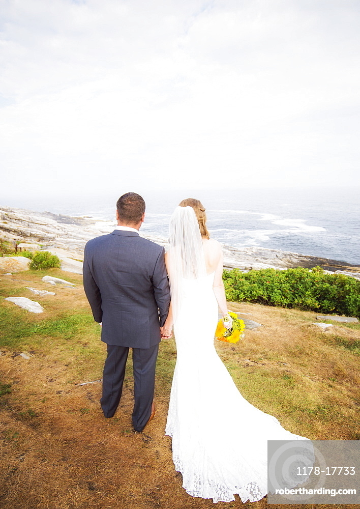 Rear view of married couple standing by sea, USA, Maine, Bristol