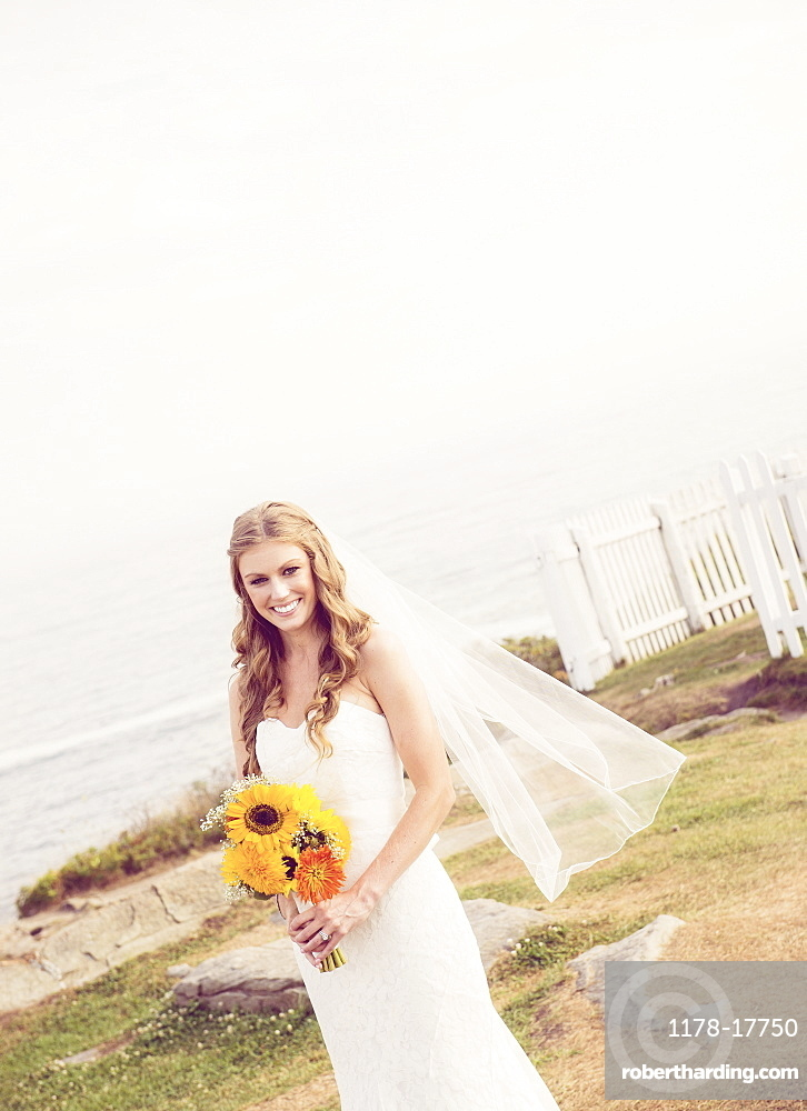 Portrait of bride holding sunflower bouquet, USA, Maine, Bristol