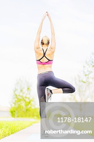Young woman doing yoga in park, Jupiter, Florida
