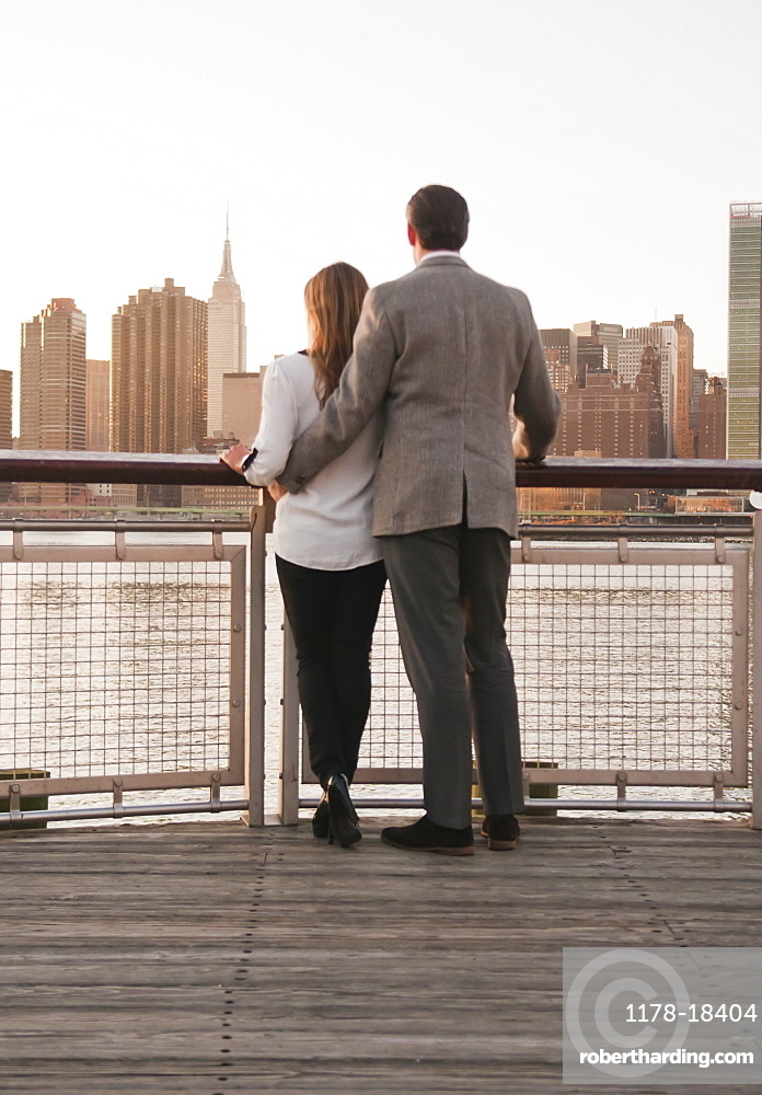 USA, New York, Long Island City, Rear view of young couple standing on boardwalk, Manhattan skyline in background