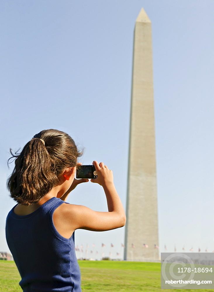 USA, Washington DC, girl (6-7) photographing Washington Monument
