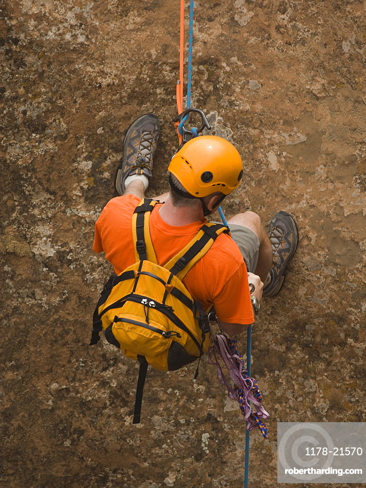 Man rappeling down cliff