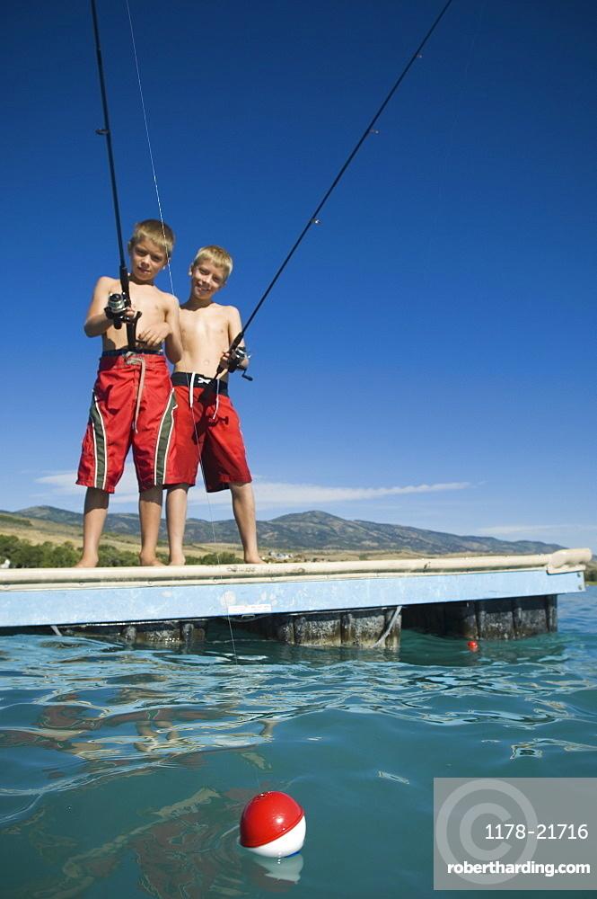Brothers fishing off dock in lake, Utah, United States