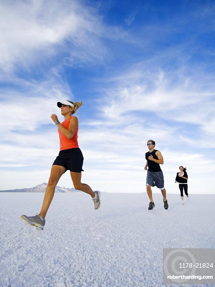 People running on salt flats, Utah, United States