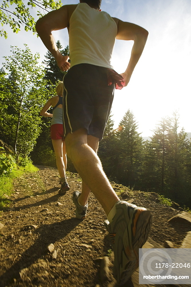 Runners ascending rocky trail
