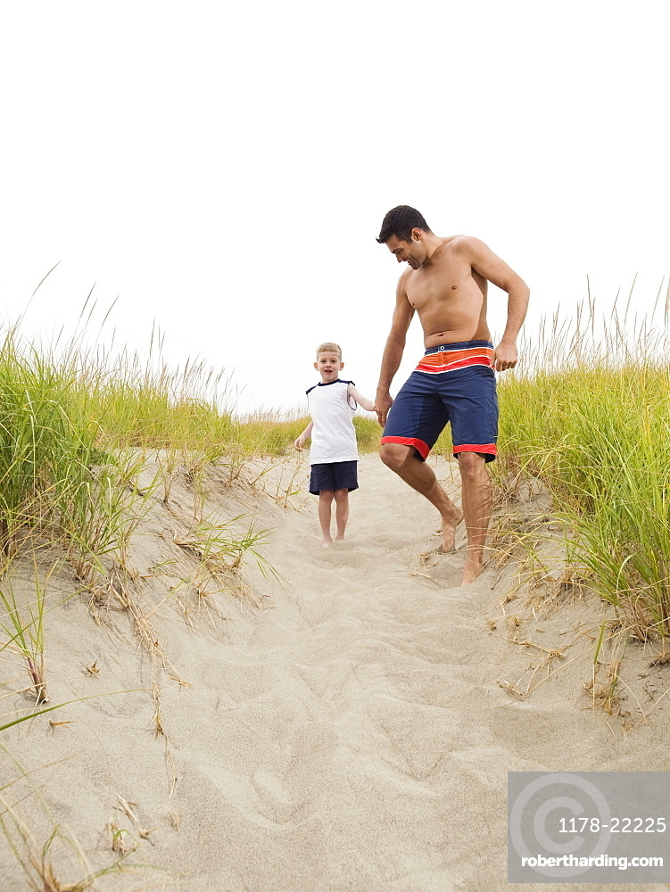 Father and son holding hands and running on beach