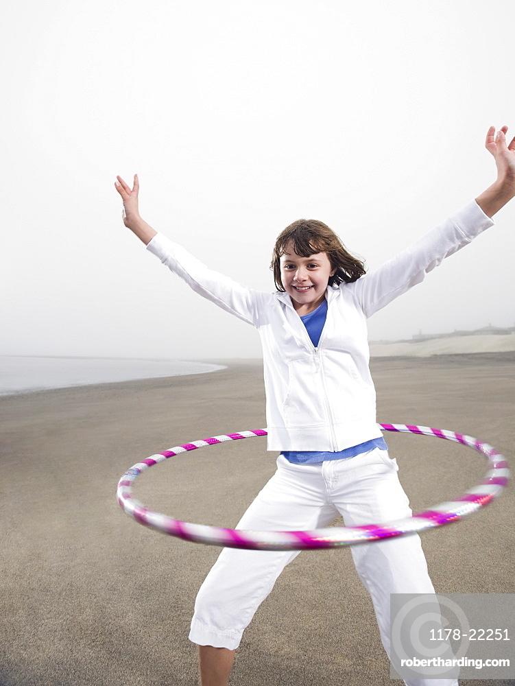 Portrait of girl with hula hoop on beach