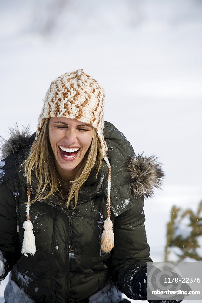A woman outdoors in snow laughing