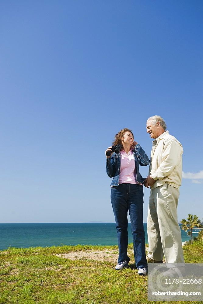 Couple looking at ocean with binoculars