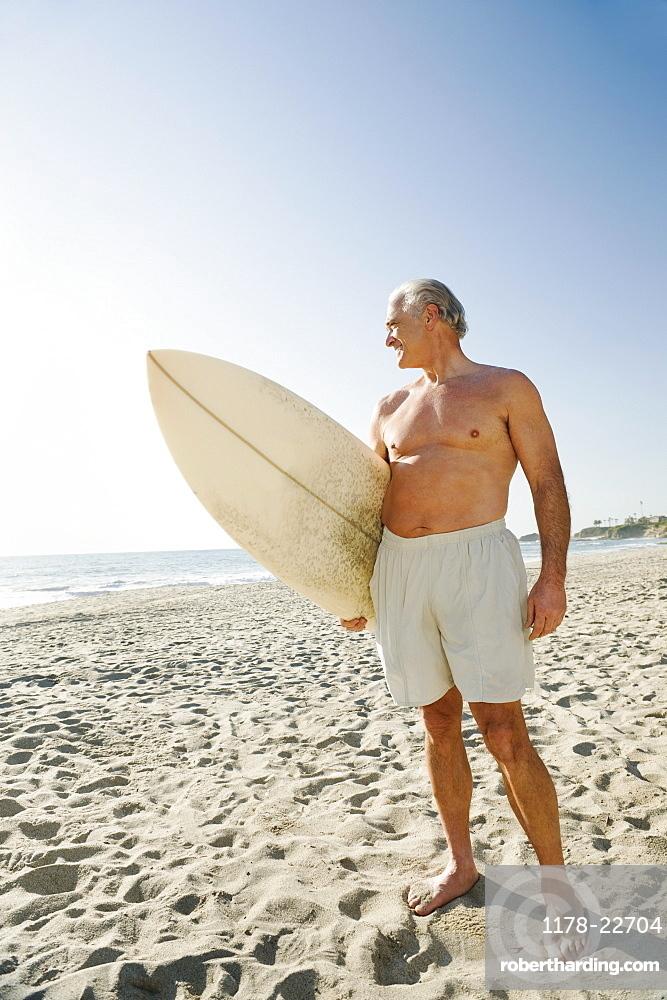 Man holding surfboard on beach