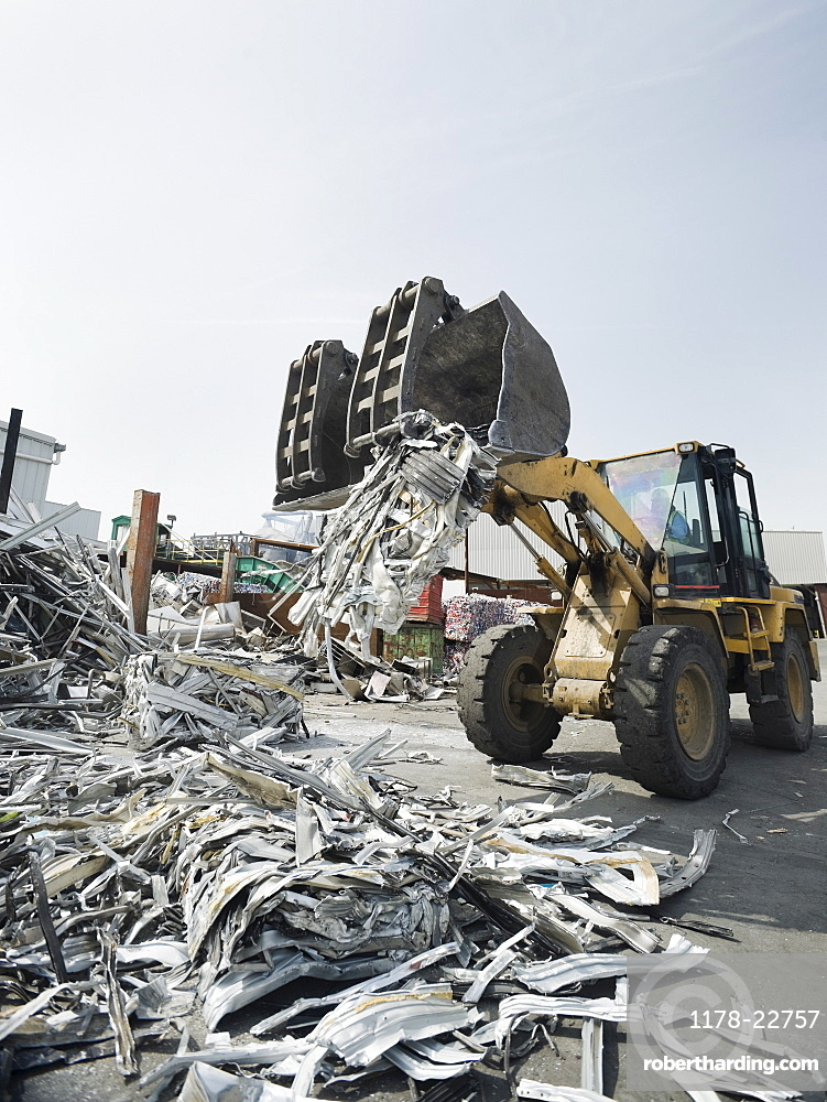 Backhoe lifting recycled metal