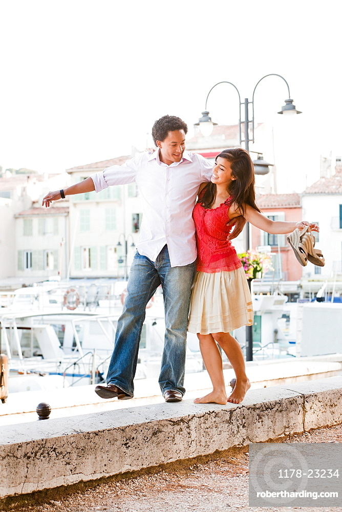France, Cassis, Couple balancing on stone wall, France, Cassis