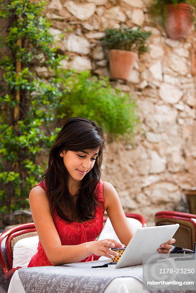 France, Cassis, Young woman using digital tablet in cafe, France, Cassis