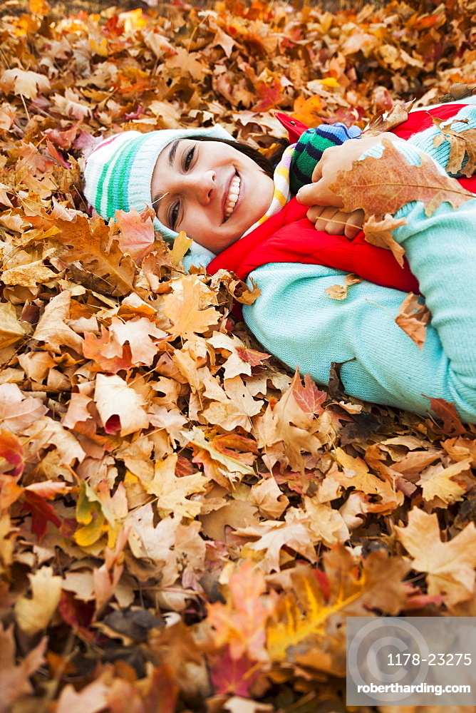 Portrait of smiling young woman lying on autumn leaves