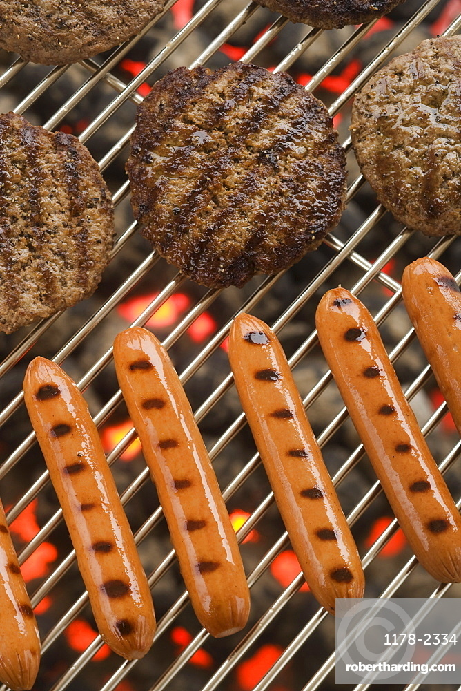 Hamburgers and hot dogs cooking on grill