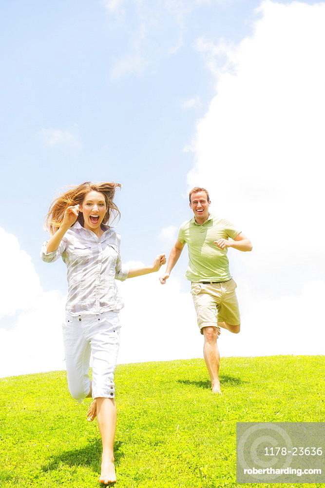 Couple running on grass, USA, New Jersey, Mendham