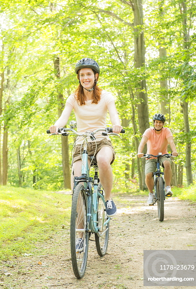 Couple cycling in forest, USA, New Jersey, Mendham