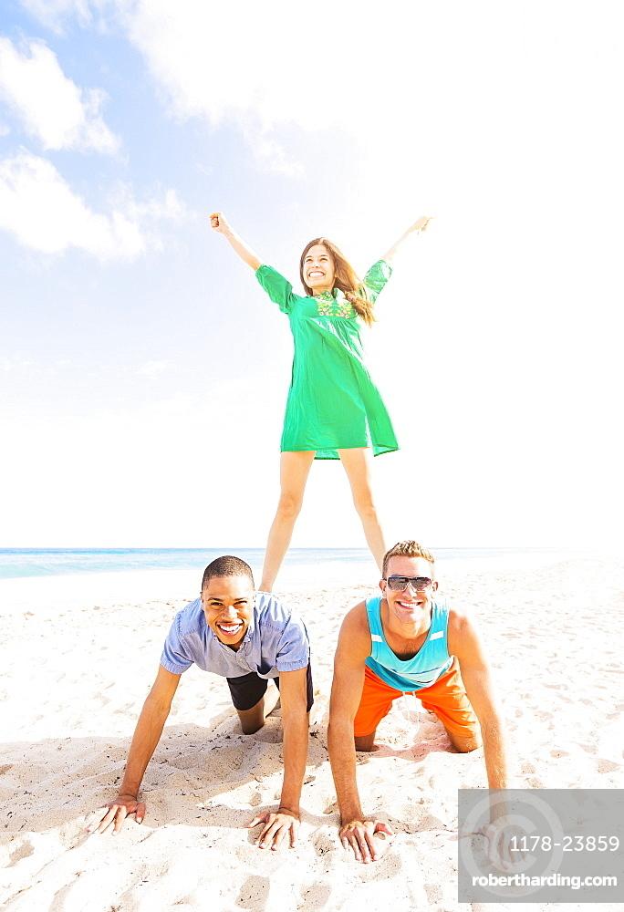 Young people making human pyramid on beach, Jupiter, Florida