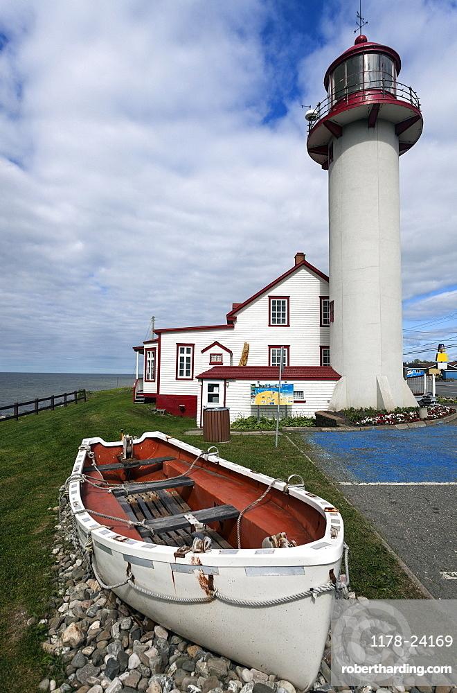 Matane Lighthouse and empty white rowboat on gravel pile, Quebec, Canada