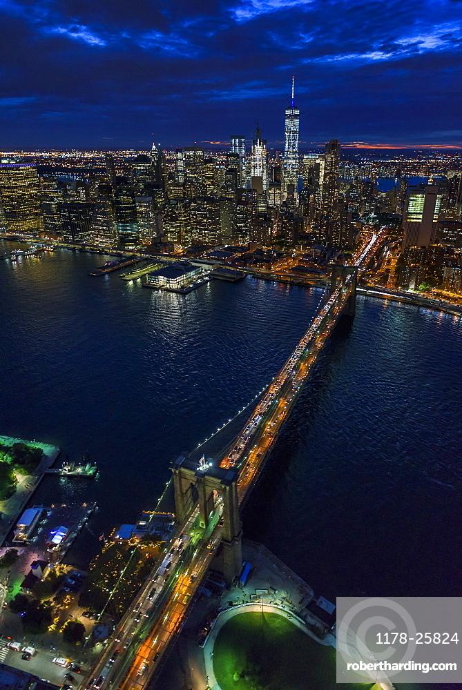 USA, New York, New York City, Manhattan, Aerial view of illuminated skyline with harbor and Brooklyn bridge at night