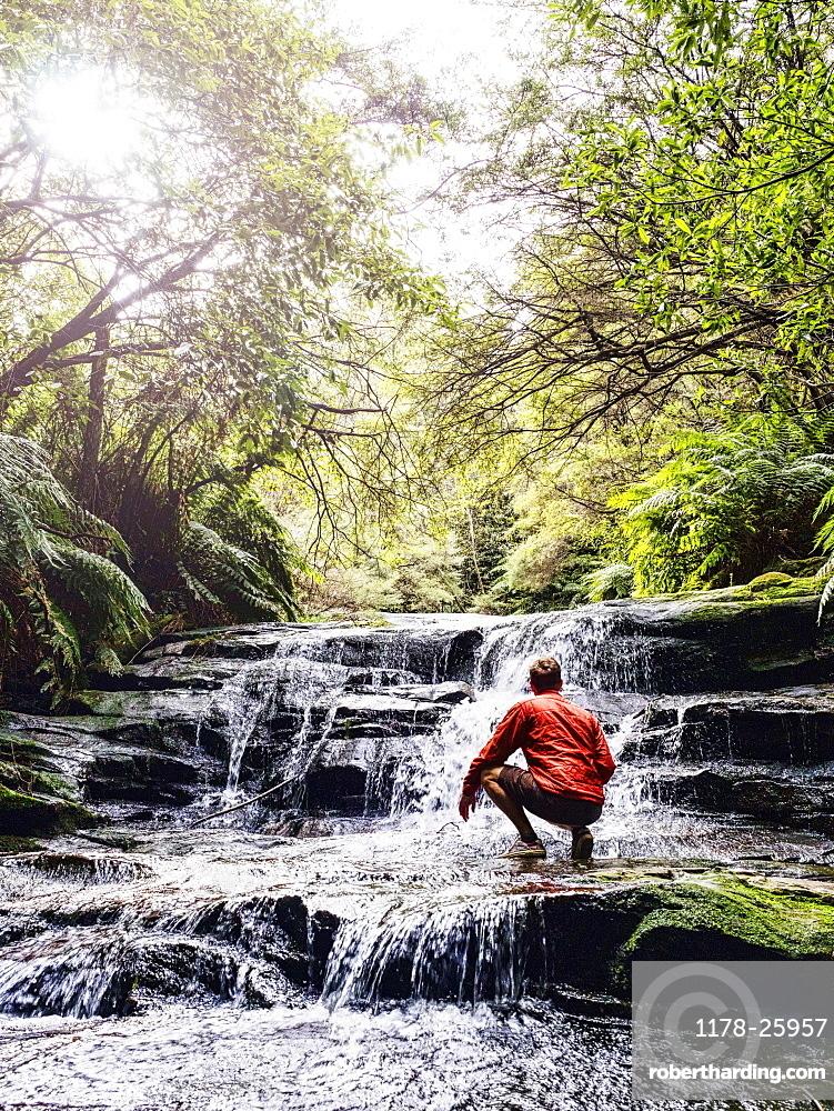 Australia, New South Wales, Katoomba, Man wading in Leura Cascade