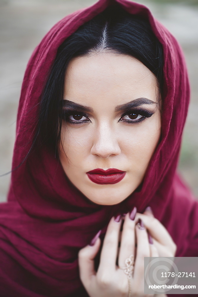Portrait of young woman wearing red lipstick and headscarf