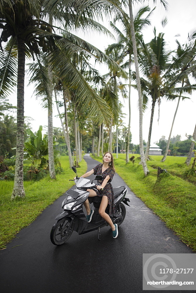 Young woman on motorcycle by palm trees in Bali, Indonesia