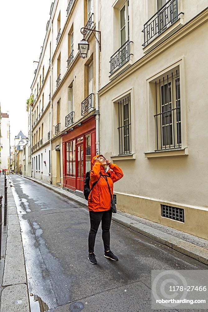 Woman wearing raincoat on street in Paris, France