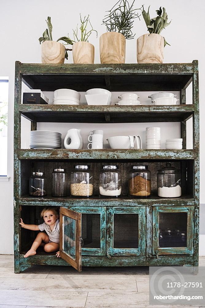 Boy hiding in cupboard in kitchen