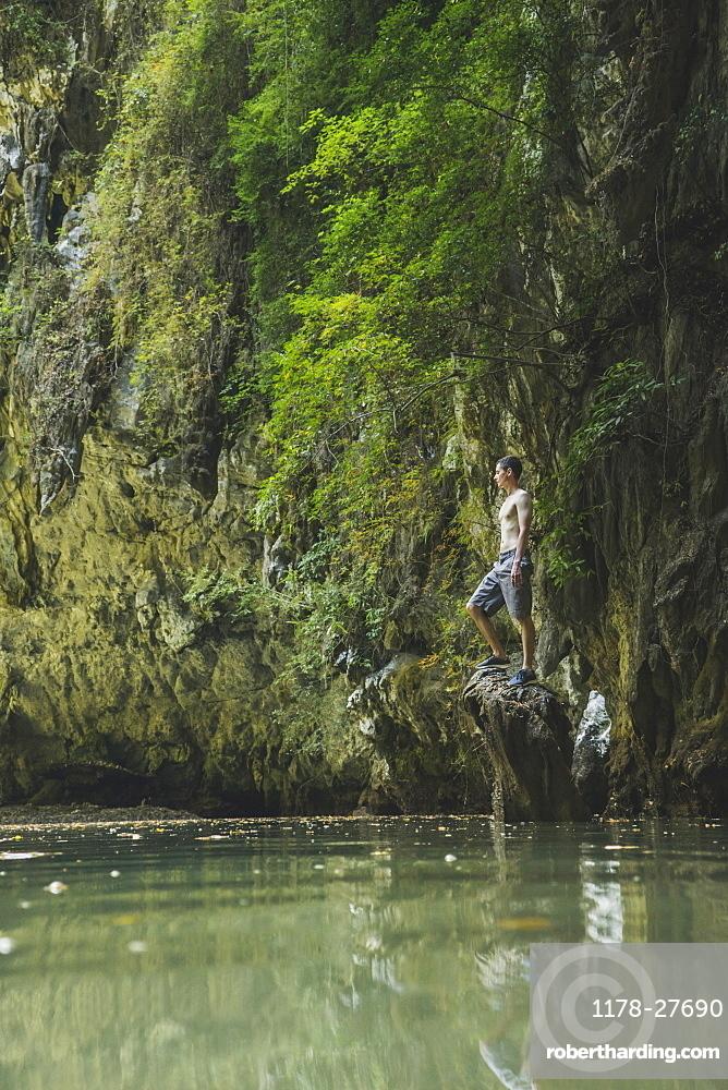 Shirtless man standing on rock in lake by cliffs in Krabi, Thailand