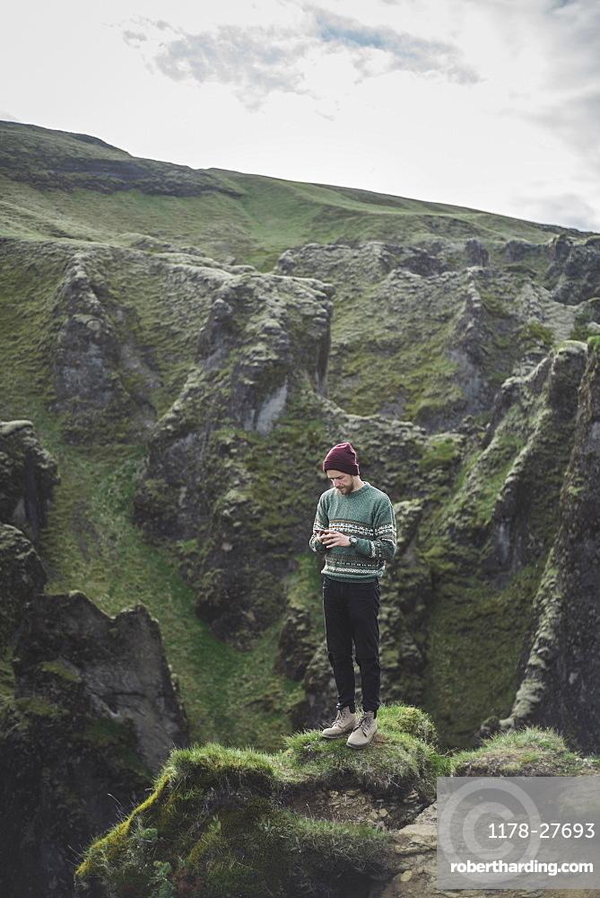 Man using smart phone on mountain in Kirkjubµjarklaustur, Iceland