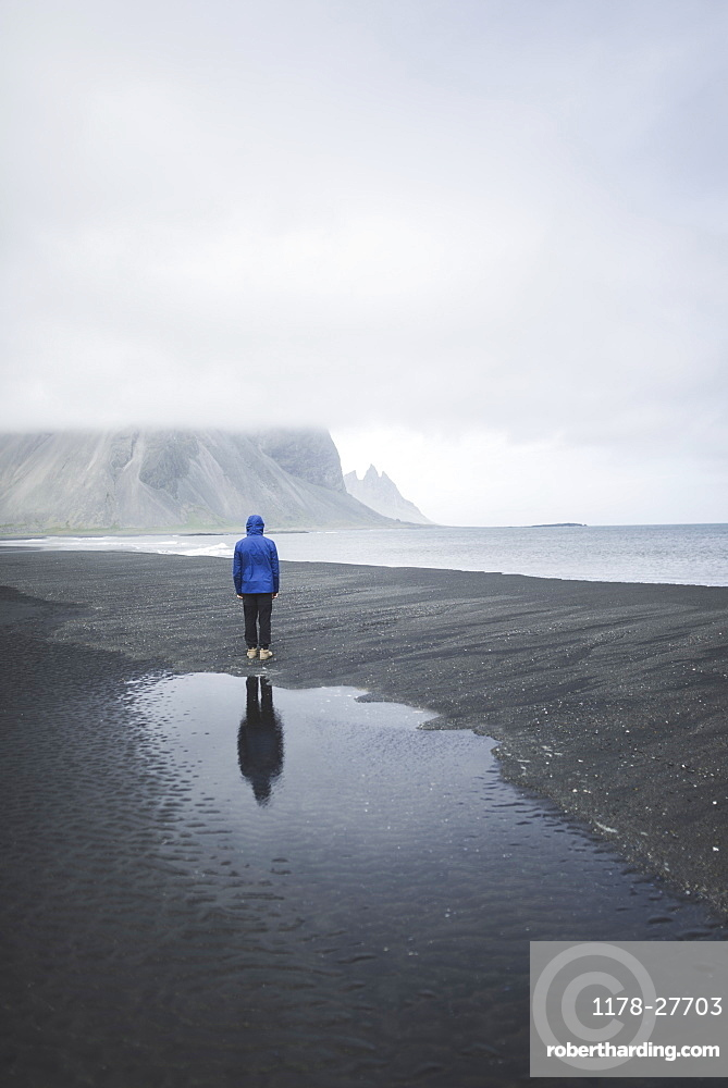Man wearing blue coat on black sand beach in Kirkjubµjarklaustur, Iceland