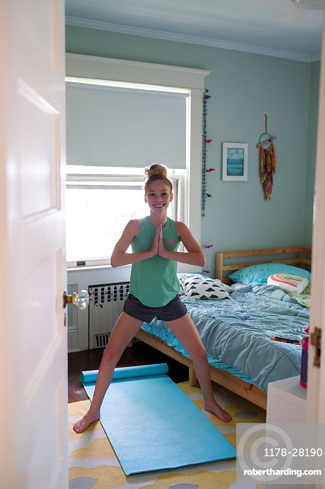 Girl doing yoga in bedroom