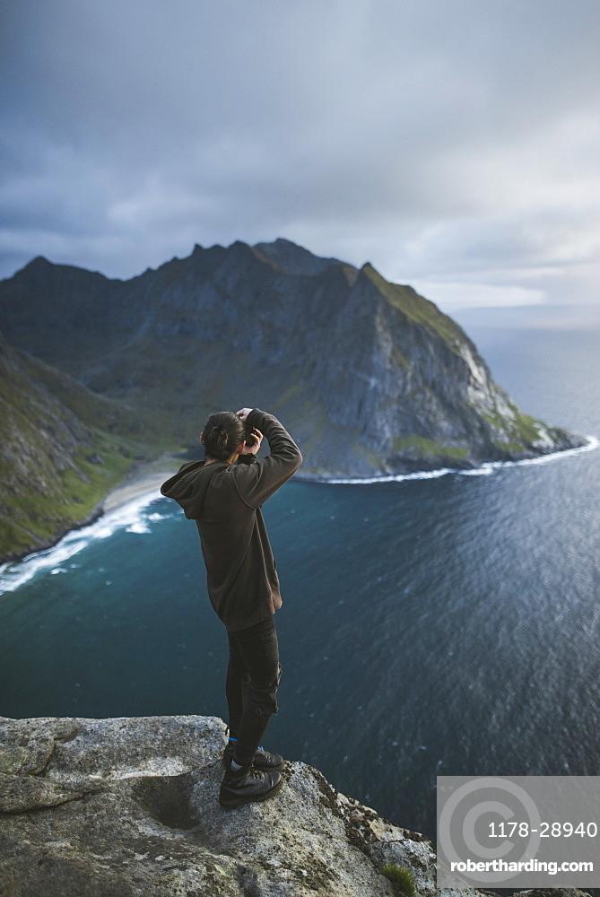 Man taking photograph on cliff at Ryten mountain in Lofoten Islands, Norway