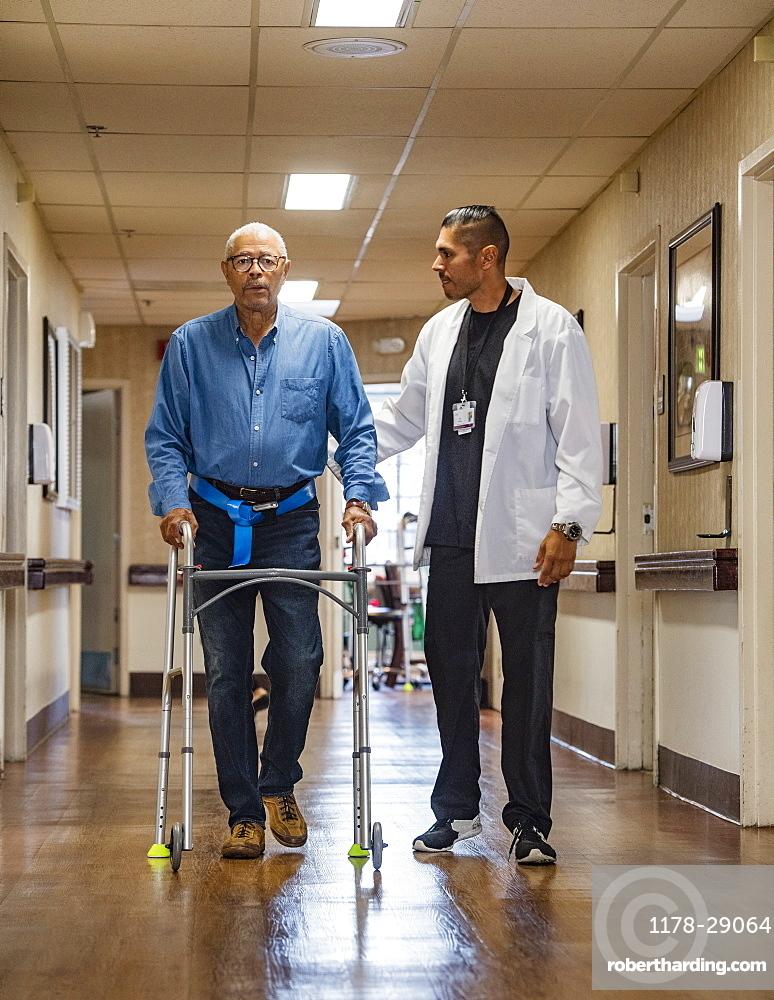 Doctor helping senior man use walking frame