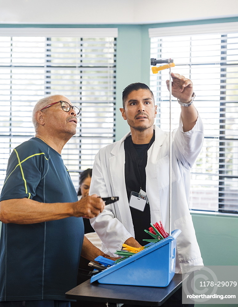 Doctor showing senior man pegs on pole at rehabilitation center