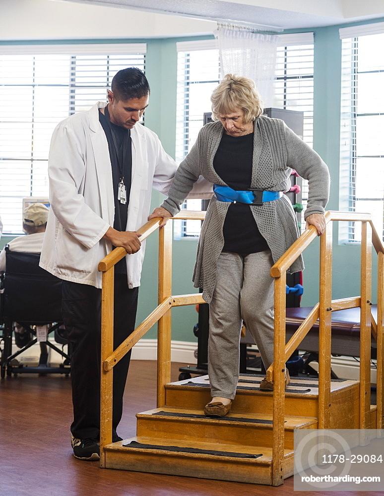 Doctor helping senior woman walk down steps
