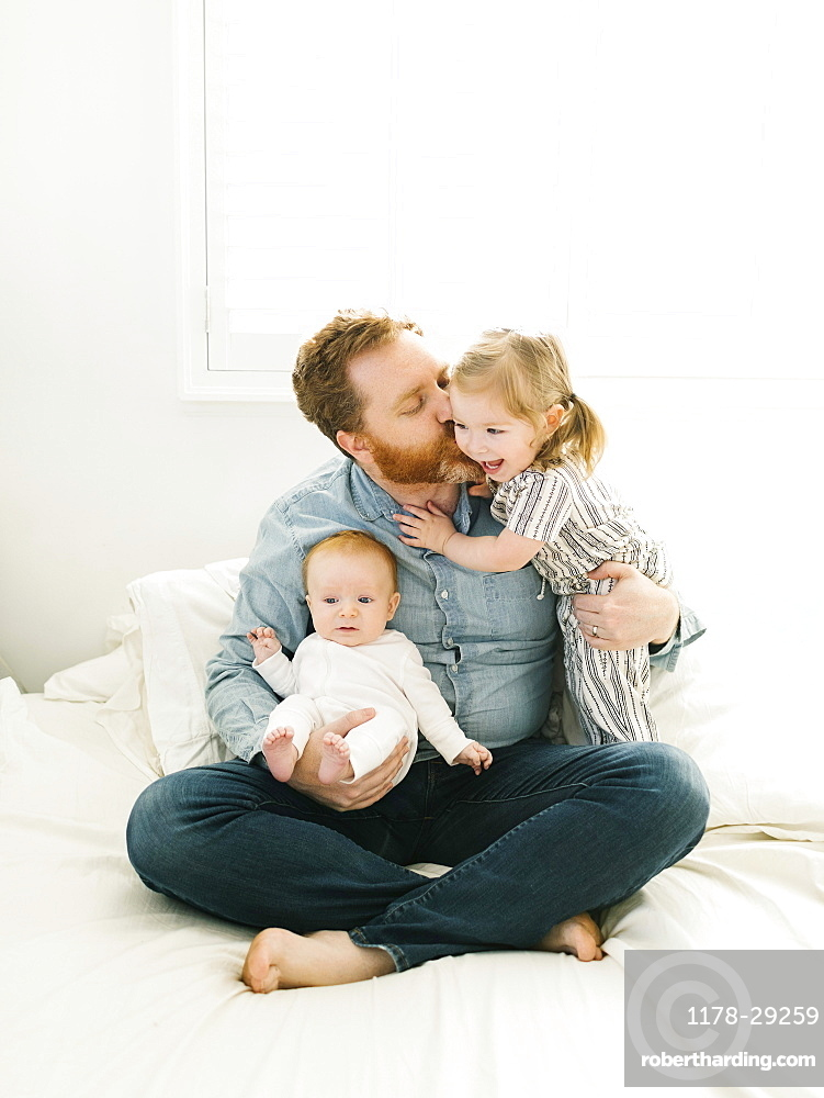 Father sitting on bed with children (2-3 months, 2-3)