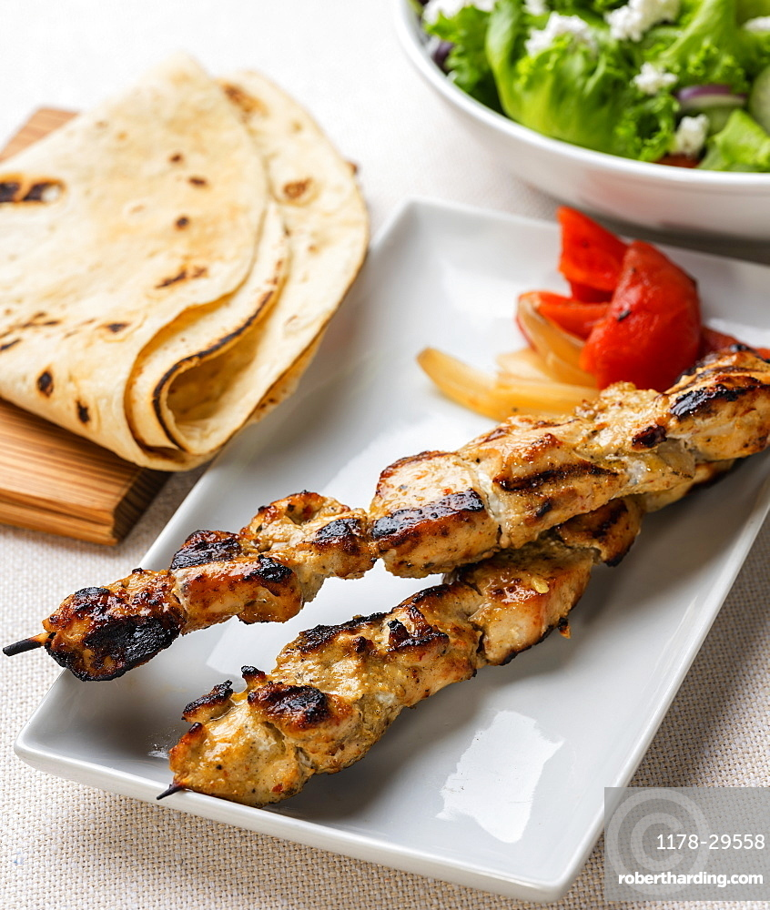 Plate of grilled chicken with pita bread and salad