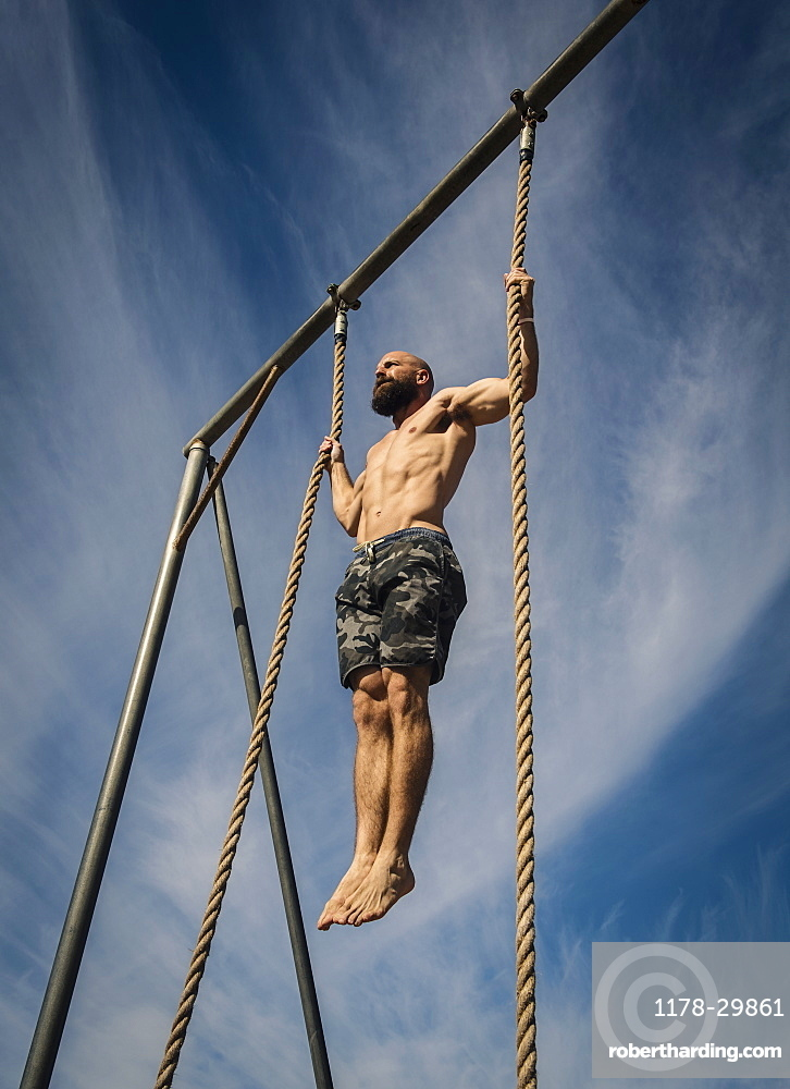 Man exercising on rope