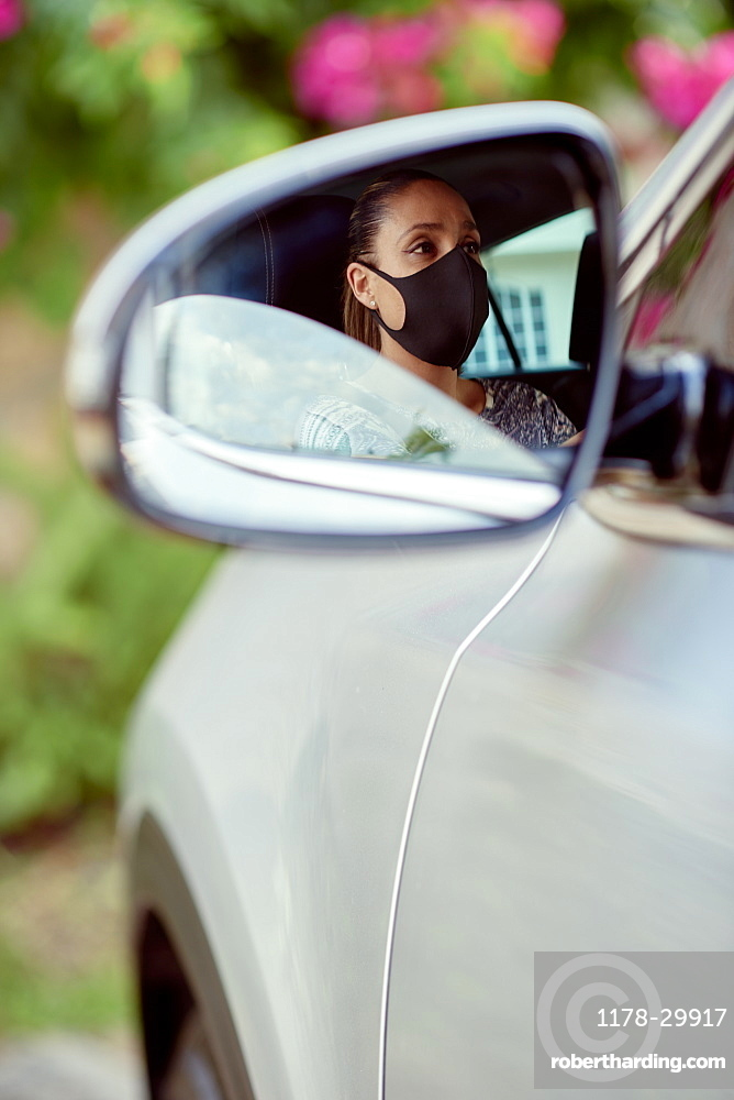 Woman with face mask driving car reflected in mirror