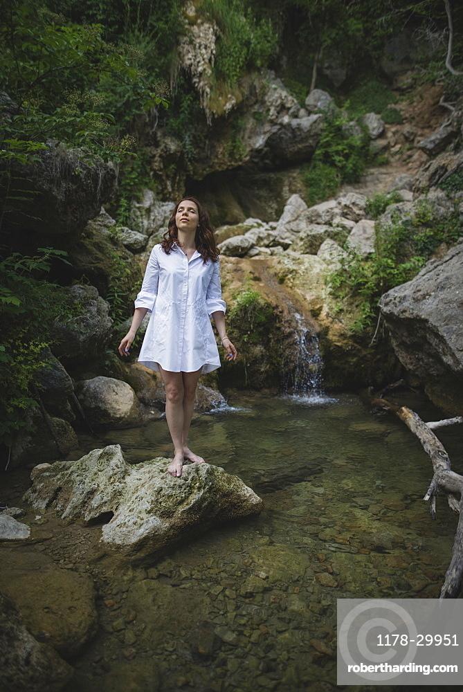 Ukraine, Crimea, Young woman standing on rock near waterfall