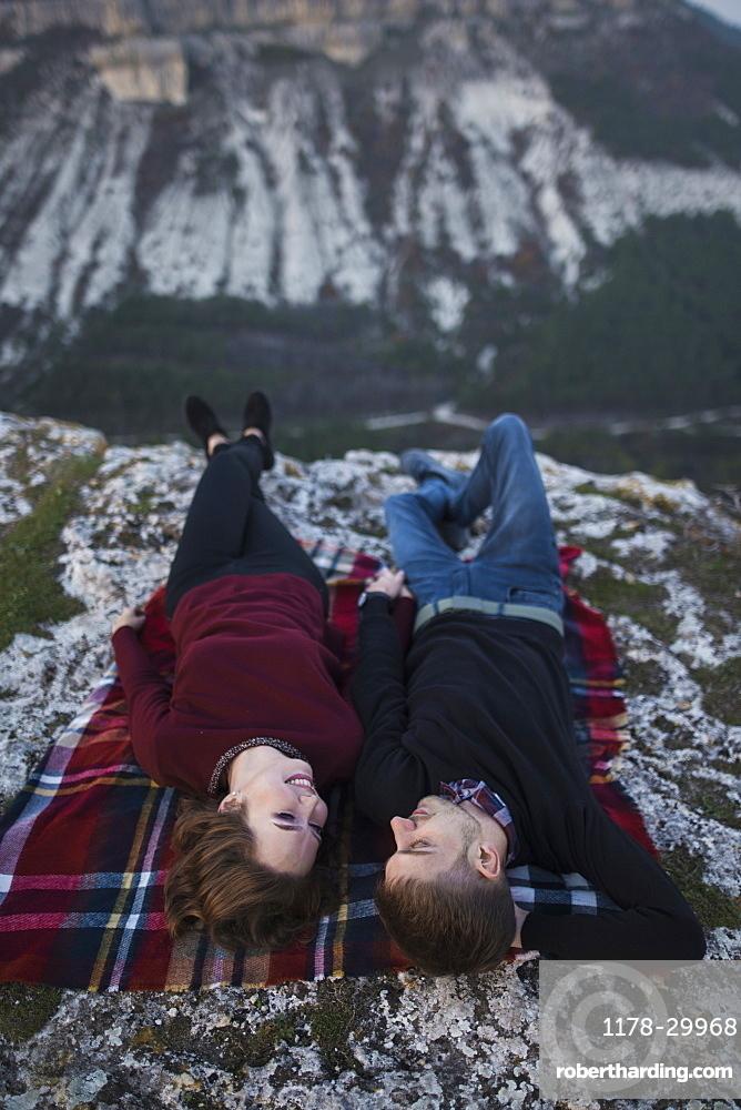 Ukraine, Crimea, Young couple lying down at plaid near canyon