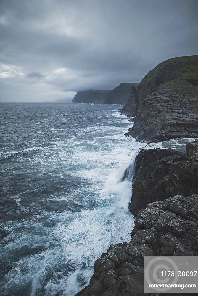Denmark, Faroe Islands, Sorvagur, Rocky sea coast with storm clouds