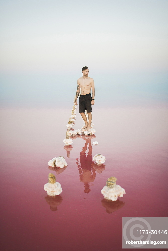 Ukraine, Crimea, Man standing on salt crystal in salt lake