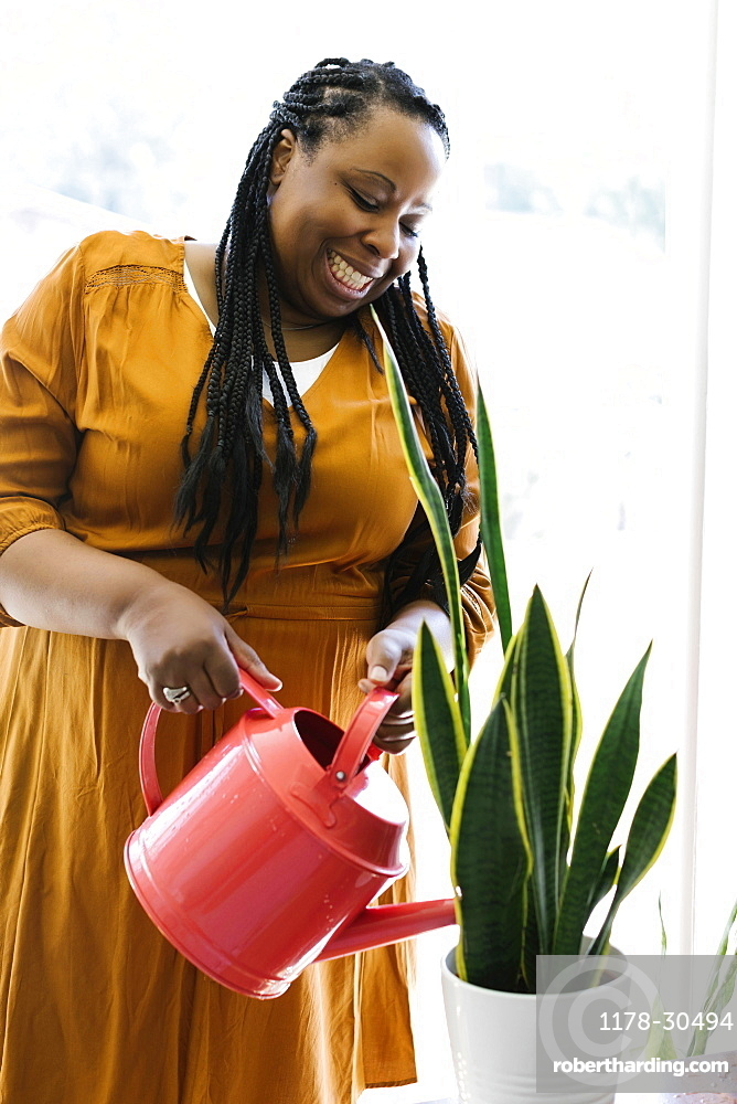 Smiling woman in orange dress watering potted plant at home